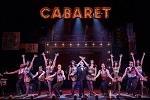 Performers on stage posing with their arms spread apart in front of a big light up sign that says Cabaret