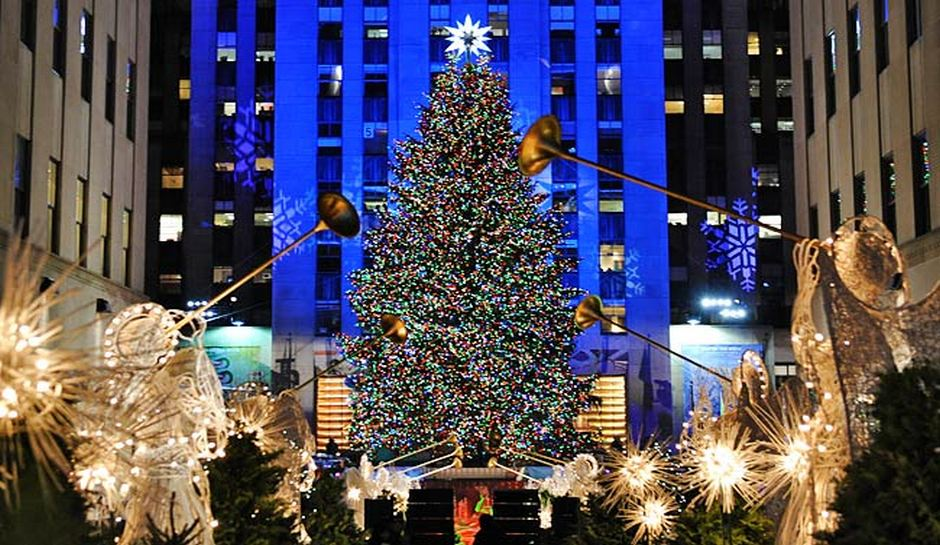 Many Bright lights attached to statue angels blowing trumpets in front of a gigantic Christmas tree in front of the Rockefeller center in New York