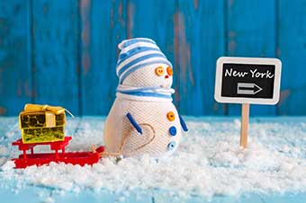 Signpost of the famous New York, USA and Snowman with red sled stand near direction sign. Christmas And new year postcard